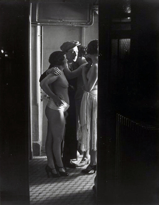 Brassai - Chez Suzy - three women around a man - 1932